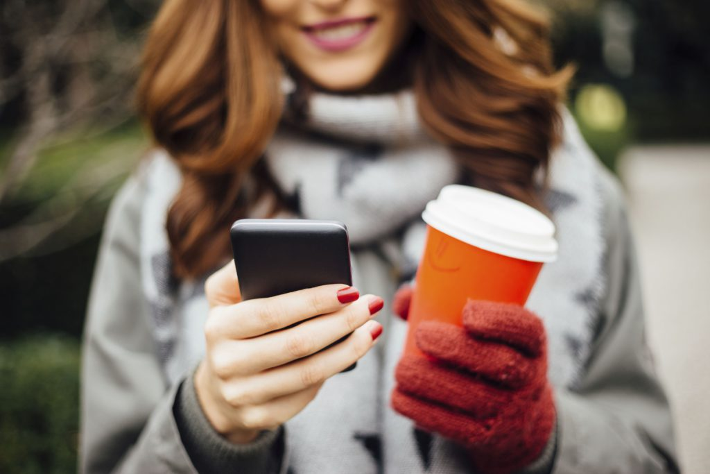 Young woman drinking coffee and using social network with her smart phone at the park during winter day.